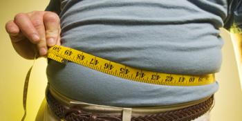 man measuring belly