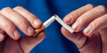Stop smoking cigarettes concept. Broken cigarette in hands. Quit bad habit, health care concept. No smoking.