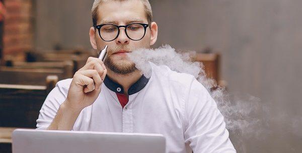 man vaping with laptop